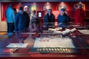 Besucher bestaunen eine mittelalterliche Urkunde im neu eröffneten Ausstellungssaal des St. Galler Stiftsarchivs. (Bild: Urs Bucher)