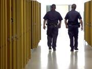 US-Polizisten patrouillieren durch den Gang mit Schliessfächern einer Schule. (Bild: KEYSTONE/AP The Citizens' Voice/KRISTEN MULLEN)
