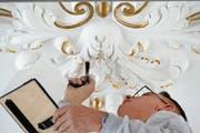 Massarbeit über Kopf: Markus Hochstrasser von der Renovationsequipe bringt Blattvergoldungen an. (Bild: Beat Christen)