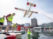 Das Wasserflugzeug Cessna 185 wird im Verkehrshaus der Schweiz in Luzern in einen Pool gehievt, dies anlässlich der Eröffnung des zweiten Teils der Ausstellung «Die Schweiz fliegt!» (Bild: KEYSTONE/URS FLUEELER)