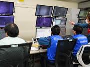 Arbeiter steuern den Roboterarm, der Brennstäbe aus dem Abklingbecken von Reaktor 3 herausholt. (Bild: Kyodo News/AP, Fukushima, 15. April 2019)