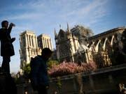 Ein Tourist macht am Mittwoch ein Foto von Notre Dame - Frankreichs Kabinett beriet gleichentags über den Wiederaufbau nach dem Brand der Kathedrale. (Bild: KEYSTONE/AP/FRANCISCO SECO)
