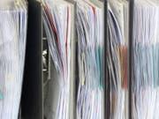 Akten stehen in einem Büro - 67,5 Prozent der Unternehmen klagen über eine hohe oder eher hohe administrative Belastung. (Bild: Keystone/DPA/MAURIZIO GAMBARINI)