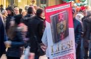 Mit einem Plakat auf dem Rücken versucht ein Teilnehmer der Koran-Verteilaktion «Lies» in Frankfurt die Aufmerksamkeit auf sich zu ziehen. (Bild: KEYSTONE/DPA/Boris Roessler)