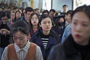 Junge Chinesen in einer U-Bahnstation in Peking während der abendlichen Hauptverkehrszeit. (Bild: Andy Wong/AP (17. April 2019))