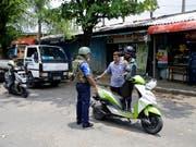 Soldaten überprüfen in Colombo Motorradfahrer. Seit den Anschlägen auf Kirchen und Hotels am Sonntag mit mindestens 359 Toten wurden insgesamt 76 Verdächtige festgenommen. (Bild: KEYSTONE/AP/ERANGA JAYAWARDENA)