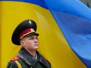 Ein ukrainischer Soldat steht Wache vor einer Landesfahne in Kiew. (Bild: KEYSTONE/EPA/SERGEY DOLZHENKO)