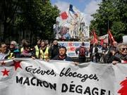 «Macron, hau ab!» heisst es auf Transparenten der «Gelbwesten», die am Samstag in Paris auf die Strasse gingen. (Bild: KEYSTONE/AP/RAFAEL YAGHOBZADEH)