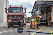 Mittels Seilzug giesst ein Feuerwehrautofahrer Wasser aus einer Spritzkanne in einen Eimer. (Bild: PD)