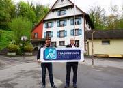 Vizepräsident Michael Schneider v/o Schruubä und Präsident Ralph Huber v/o Daffy präsentieren vor dem Pfadiheim Alte Mühle das neue Vereinslogo. (Bild: PD)