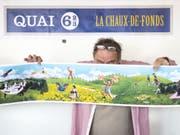 Jacques Froidevaux vom Künstlerkollektiv Plonk & Replonk posiert mit dem Entwurf eines Monumentalgemäldes, das in La Chaux-de-Fonds installiert werden soll. Anlass ist die 2009 erfolgte Aufnahme der Stadt in die Liste der UNESCO-Welterbestätten 2009. (Bild: Keystone/ADRIEN PERRITAZ)