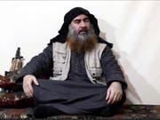 In dem Video sitzt al-Bagdadi mit gekreuzten Beinen auf einem Kissen vor einer Waffe und spricht zu mehreren Anhängern der Terrormiliz. Darin erklärt er unter anderem, der Kampf gegen die «Kreuzfahrer» werde lange dauern. (Bild: Keystone/AP)