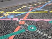 Die farbigen Linien anstelle der aufgehobenen Parkplätze auf dem Marktplatz gehören zu einem Spiel für Erwachsene und Kinder. (Bild: Reto Voneschen - 2. April 2019)