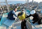In luftiger Höhe entfernen Handwerker die vergoldete Kugel von der Kirchturmspitze. (Bild: Fritz Heinze)