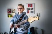 In seinem Zimmer übt Nevio täglich auf seiner Gitarre. Eine Wand hat er geschmückt mit Autogrammkarten und Fotos von «The Voice». (Bild: Michel Canonica)