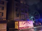Nächtlicher Brand an der Sonnenstrasse in St. Gallen: Wegen des dichten Rauchs aus der brennenden Wohnung im ersten Stock flüchteten mehrere Bewohner unter das Dach des Hauses. (Bild: Kantonspolizei St. Gallen)