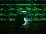 Ein Bitcoin-Schürfer nimmt die Mining-Maschinen in einer chinesischen Provinz in Augenschein. Die chinesische Regierung will das Schürfen von Digitalwährungen unterbinden. (Bild: KEYSTONE/EPA/LIU XINGZHE/CHINAFILE)