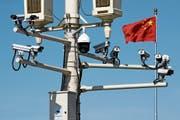 Chinesische Flagge hinter Überwachungstechnik: Peking exportiert fleissig Überwachungssysteme. Bild: Andy Wong/AP (Peking, 15. März 2019)