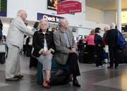 Britische Fluggäste warten beim Check-In auf die Weiterreise. (Scott Heppell/AP)