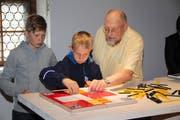 Spielerfinder Urs Wüthrich beobachtet, ob seine beiden Grosskinder, Micha (links) und Luzian Wüthrich, das Spiel richtig demonstrieren. (Bild: Paul Gwerder, Bürglen, 11. Mai 2019)
