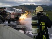 Ein Kleinflugzeug brennt, ein Feuerwehrmann greift ein: Notfallübung auf dem Flugplatz in Thun. (Bild: Keystone/ANTHONY ANEX)