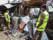 Die Polizei bei einem von dutzenden mutmasslich von Singhalesen zerstörten Läden muslimischer Besitzer in Sri Lanka. (Bild: Keystone/AP/CHAMILA KARUNARATHNE)
