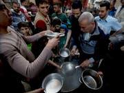 Essensausgabe durch eine Hilfsorganisation in Gaza Stadt zum Fastenbrechen während des Ramadan. (Bild: KEYSTONE/AP/HATEM MOUSSA)