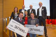 Raphael Frei (links) und Markus Kopf halten die Preischecks; dahinter der Stiftungsrat der Carl-Stürm-Stiftung. (Bild: Christof Sonderegger)