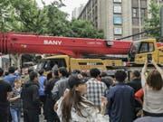 Schaulustige beobachten die Ankunft eines LKW-Hebekrans nach dem Einsturz eines Gebäudes in der Nähe. (Bild: Keystone/AP CHINATOPIX)