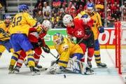 Die Schweizer Tristan Scherwey (links) und Gaetan Haas (Mitte, im roten Dress) kämpfen gegen die Schweden vor deren Tor. (Bild: Andy Müller/Freshfocus, Bratislava, 18. Mai 2019)