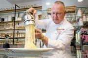 Spaghetti-Eis-Erfinder Dario Fontanella drückt in seinem Eiscafé Vanilleglace durch eine Spätzlepresse. (Bild: Bilder: Thomas Lohnes/Imago-Images (Mannheim, 18. Februar 2019))
