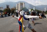 Ein regierungskritischer Demonstrant in Caracas wirft einen Stein in Richtung der Sicherheitskräfte. (Bild: Ariana Cubillos/AP, 1. Mai 2019)