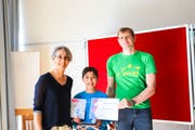 Levin Münger (mitte) nimmt die Urkunde mit der Goldmünze entgegen. Die Lehrerin Arlette von Groddeck und Dima Nikolenkov vom Verein Känguru Schweiz gratulieren dem 10-Jährigen. (Bild: Dinah Hauser)