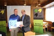 Der neue Präsident der Arbeitgebervereinigung der Region Toggenburg (ART), Samuel Schiess (links) überreicht seinem Vorgänger Philippe Schiess ein Geschenk zum Dank für den Einsatz für die ART. (Bild: Martin Knoepfel)