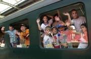 Kinder winken aus einem Zug. (Bild: Keystone)