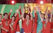 Doppeltorschütze Robert Lewandowski hebt den Cup-Pokal, seine Teamkollegen feiern mit. (Bild: Jan Woitas/Keystone (Berlin, 25. Mai 2019))