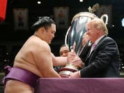 US-Präsident Trump überreicht dem Sieger des Sumo-Ringer-Turniers den eigens dafür geschaffenen «President's Cup». (Bild: KEYSTONE/EPA JIJI PRESS)