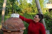 Imkerin Alice Oberli prüft, ob sich in dem Weissenseifener Hängekorb noch Bienen befinden. Der Korb besteht aus Stroh und Lehm. (Bild: Ines Biedenkapp)