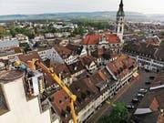 Arbeiter installieren auf dem Turm der evangelischen Stadtkirche ein Storchenrad. (Bild: PD/Thomas Moos (Toggenburger + Co AG))