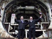 Die beiden Ingenieure Philippe Cozette (Franzose mit britischem Fähnlein) und Graham R. Fagg (Brite mit französischem Fähnlein) posieren zehn Jahre nach dem historischen Durchbruch vor der Eurotunnel-Bohrmaschine in Folkestone. (Bild: Hugo Philpott/Keystone, 1. Dezember 2000)