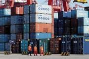 Arbeiter passieren gestapelte Container in einem Containerhafen in Qingdao in der ostchinesischen Provinz Shandong. (Bild: AP)