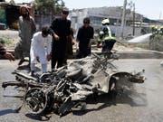Menschen in Kabul sehen sich das Wrack des Autobombers an. (Bild: KEYSTONE/EPA/JAWAD JALALI)