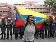 Eine Oppositionsanhängerin vor dem Hauptquartier der Marine in Caracas. (Bild: KEYSTONE/AP/MARTIN MEJIA)