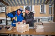 Mit Mütze und Schal: Zwei Männer schrauben am Maimarkt einen Nistkasten zusammen. (Bild: Benjamin Manser)