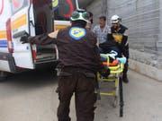 Die oppositionelle Zivilschutztruppe Weisshelme bringen einen verletzten Mann in Ehssem, im Süden der Provinz Idlib, ins Spital. (Bild: KEYSTONE/AP Syrian Civil Defense White Helmets/UNCREDITED)