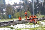 Arbeiter schrauben den am Trageseil hängenden Mast auf dem Fundament fest. (Bild: Martin Knoepfel)