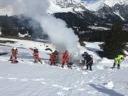 Einsatzkräfte schaufelten die brennende Fräse mit Schnee zu. (Bild: Kapo GR)