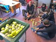 Freiwillige schneiden die alten Tennisbälle auf, damit sie mit Traubenzucker und Flyer gefüllt werden können. (Bild: PD)