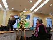 Die Gemeinderätinnen Veronika Färber und Anna Rink enthüllen das Gemälde, das die Fraktion Freie Liste/Rägeboge dem scheidenden Kollegen Christian Forster schenken will. Er war an der Sitzung nicht anwesend. (Bild: Martina Eggenberger)