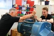 Ausbildner Kaspar Furrer und Lehrling Michael Glesti reparieren einen Motor samt Getriebe. /Bild: Werner Lenzin)